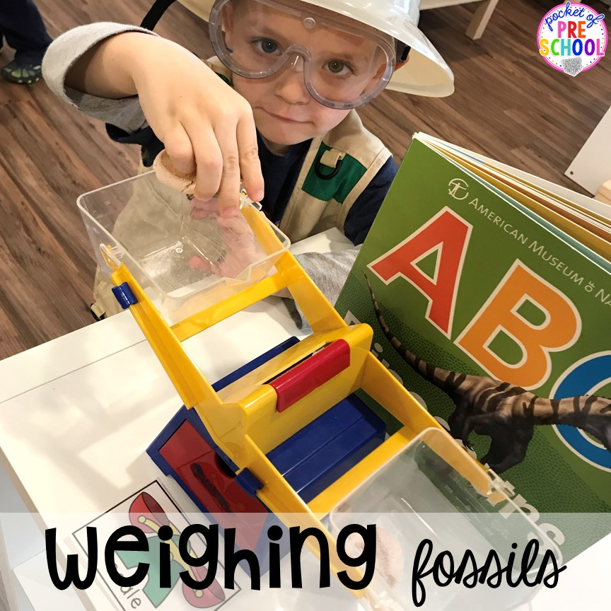 Weighing the fossils! ow to make a Dinosaur Dig Site in dramatic play and embed tons of math, literacy, and STEM into their play. Perfect for preschool, pre-k, and kindergarten. #preschool #prek #dinosaurtheme #dinodig #dramaticplay